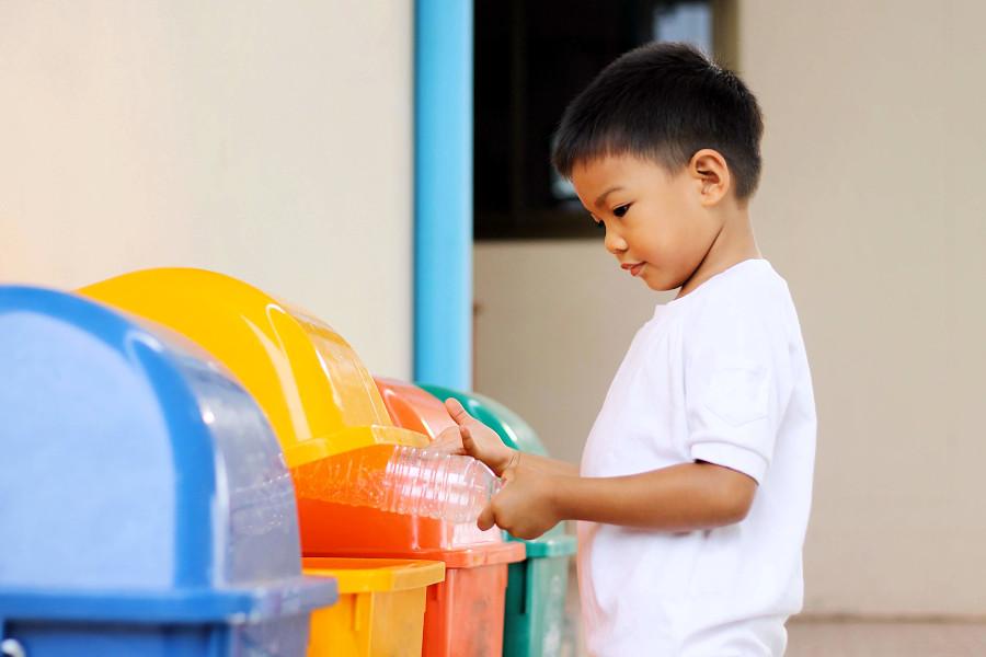 chłopiec segreguje śmieci wyrzuca butelkę