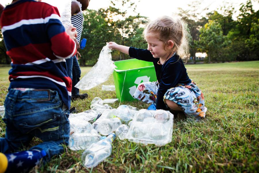 Dziewczyna segreguje plastik w ogrodzie
